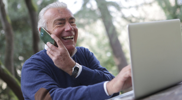 Older gentleman using phone and computer